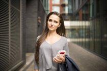 Молодая бизнесвумен со смартфоном за пределами офиса, Лондон, Великобритания — стоковое фото