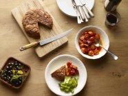 Vista superiore della tabella con tortilla di patate spagnola e ciotola di pomodori — Foto stock
