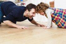 Uomo maturo strisciando testa a testa con figlia sul pavimento della cucina — Foto stock