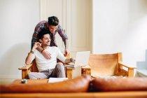 Junger Mann zu Hause sitzen auf Stuhl, mit Laptop, seine Partnerin umarmt ihn von hinten — Stockfoto