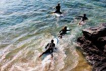 Четыре человека на доски для серфинга в воде — стоковое фото
