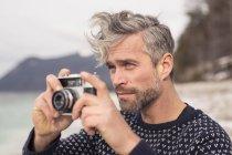 Взрослый мужчина на улице, держит камеру, фотографирует пейзажи, Немецкие Альпы, Германия — стоковое фото
