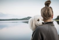 Coton de tulear dog looking over woman's shoulder at lake, Orivesi, Finland — Stock Photo
