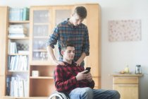 Young man using wheelchair reading smartphone texts in kitchen — Stock Photo