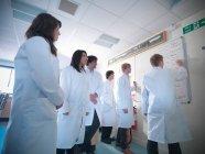 Научные студенты, пишущие на доске в школьной лаборатории — стоковое фото