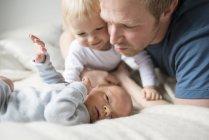 Vater und Big Brother blickte auf Babyjungen lächelnd — Stockfoto