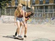 Two women practising skateboarding balance in skatepark — Stock Photo