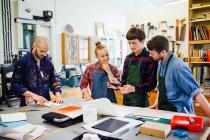 Gruppo di giovani artigiani che utilizzano tablet digitale nel workshop di arte del libro — Foto stock