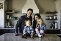 Portrait of mid adult parents with girl and baby boy on kitchen counter — Stock Photo