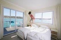 Хлопчик стрибає на ліжку в houseboat, Kraalbaai, Південно-Африканська Республіка — стокове фото