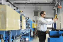 Manager monitoring information on industrial machinery — Stock Photo