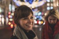Jeune femme debout dans la rue éclairée, souriant — Photo de stock