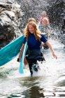 Quatre personnes portant des planches de surf — Photo de stock