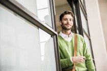 Retrato de hombre de negocios fresco y confiado apoyado en la puerta de la oficina - foto de stock