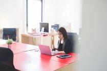 Jovem mulher na mesa de escritório digitando no laptop — Fotografia de Stock