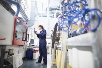 Female engineer monitoring automated machinery using digital tablet — Stock Photo