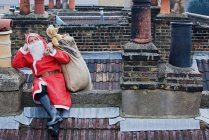 Santa claus sitting on a roof — Stock Photo