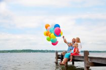 Famiglia che tiene palloncini sul molo di legno — Foto stock