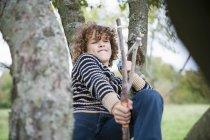 Хлопчик з катапульти, сидячи на дереві — стокове фото