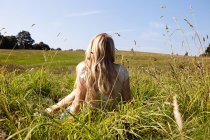 Jeune femme assise dans un champ avec le dos à la caméra — Photo de stock