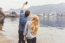 Coppia giovane che prende selfie smartphone sul lungolago, Lago di Como, Italia — Foto stock