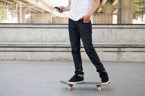 Adolescent sur planche à roulettes avec téléphone portable — Photo de stock