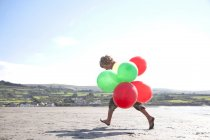 Boy on beach holding balloons, Wales, UK — Stock Photo