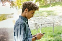 Teenage boy using cell phone — Stock Photo