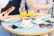 Beschnitten, Aufnahme von zwei jungen Frauen Essen Frühstück Baguette im Straßencafé, Paris, Frankreich — Stockfoto
