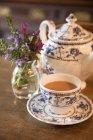 Mesa con tetera tradicional y taza de té con leche - foto de stock
