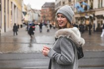 Portrait d'une femme adulte mid en tricot bonnet regardant en arrière sur la rue de la ville — Photo de stock
