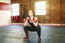 Donna squatting sollevamento kettlebells — Foto stock