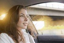 Молодая женщина в машине, волосы дуют на ветру — стоковое фото