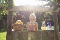 Portrait of girl on lemonade stand holding up one dollar bill — Stock Photo