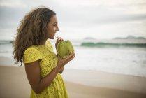 Junge Frau trinkt Kokosmilch am Strand von Ipanema, Rio De Janeiro, Brasilien — Stockfoto