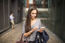 Young businesswoman texting on smartphone outside office, London, UK — Stock Photo