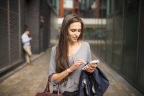 Junge Geschäftsfrau SMS auf dem Smartphone außerhalb des Büros, London, Großbritannien — Stockfoto