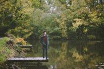 Юнак стояв на краю річки пристані — стокове фото