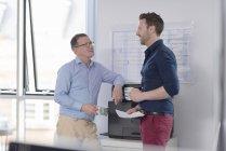 Два офисных работника разговаривают, стоя в офисе на принтере, человек держит бумажный документ — стоковое фото