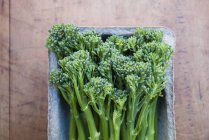 Tub of fresh broccolini on table, top view — Stock Photo