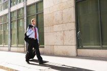 Uomo d'affari rotolamento bagagli all'aperto, attenzione selettiva — Foto stock