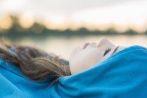 Giovane donna con cappuccio blu sdraiata, primo piano — Foto stock
