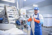 Porträt eines Arbeiters in einer Lebensmittelfabrik, der frischen Lachs neben Maschinen hält — Stockfoto