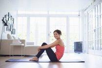 Retrato de mulher adulta média no tapete de ioga na sala de estar — Fotografia de Stock