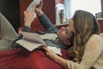 Casal deitado na cama lendo a papelada — Fotografia de Stock