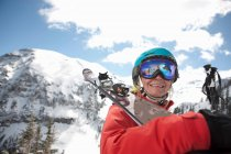 Young woman in skiwear holding skis over shoulder, smiling — Stock Photo