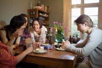 Друзі сміялися за обіднім столом — стокове фото