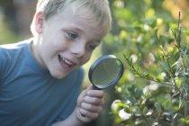 Мальчик обнаруживает растения с лупой в саду — стоковое фото