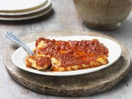 Queso feta al horno con salsa de tomate secada al sol, en un tazón con cuchara - foto de stock