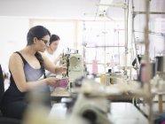 Trabajadoras de la confección en fábrica de ropa - foto de stock